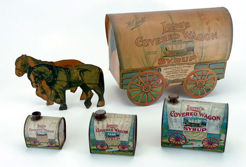 A highlight from the Ernie and Ida Long collection is this group of items from the San Francisco producer of maple syrup. Three sizes of figural tin containers in the shape of covered wagons will be sold, along with a cardboard adverting replica of a covered wagon. To Noel Barrett's knowledge, only one or two example of the smallest size of tin shown here is known to exist. Noel Barrett Auctions image.
