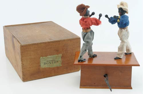 Coming from an Australian consignor, a classic American toy by Ives - African-American mechanical boxers on a wood platform - sold with its original wood box for $10,450. Image courtesy Noel Barrett Auctions.