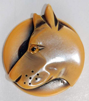 A big dog's head was carved into this celluloid button. Image courtesy of Bella Button Auctions.