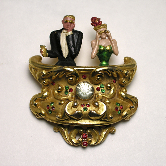 """1934 Lucien Lelong brooch in gilt metal with enamel and jewel detail. Signed Mosell, engraved <em>Lucien Lelong – Opening Night</em>. 2 5/8 inches. $3,000-$4,000″ title=""""1934 Lucien Lelong brooch in gilt metal with enamel and jewel detail. Signed Mosell, engraved <em>Lucien Lelong – Opening Night</em>. 2 5/8 inches. $3,000-$4,000″ class=""""caption"""" /><br /><div id="""
