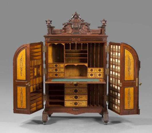 The Wooton secretary is pictured in the open position with its writing surface lowered. The compartments on either side of the main case swing closed when the desk is not in use. The Extra Grade model is estimated at $25,000-$40,000. Image courtesy New Orleans Auction, St. Charles Gallery Inc.