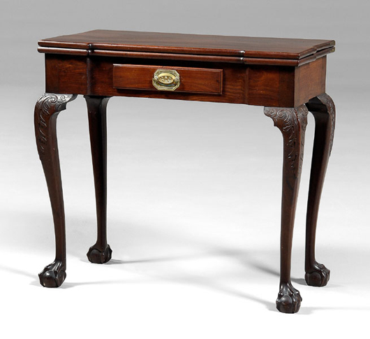 The grandson of Jonathon Harwood, Littleton, Massachusetts, consigned this 28 ½ inch by 32 inch by 15 inch Boston Chippendale game table. With fold-over mahogany top, cabriole legs with acanthus carved knees and ball and claw feet, it was the top furniture lot at $74,750.