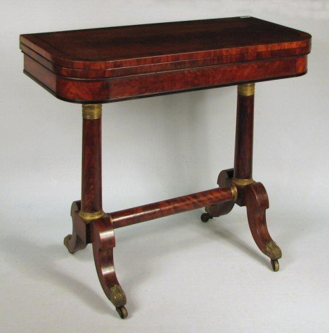 Attributed to Duncan Phyfe, New York, circa 1820, this classical figured mahogany card table features carved and inlaid sabre legs ending in foliate brass casters. It has a $4,000-$6,000 estimate. Image courtesy Woodbury Auction LLC.