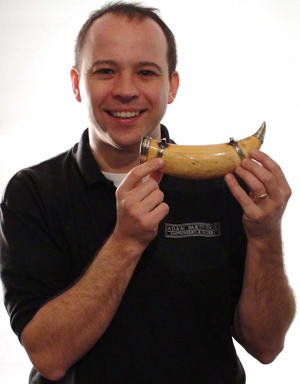 Auctioneer Adam Partridge holds the rare scrimshaw whale tooth. Image courtesy Adam Partridge Auctioneers.