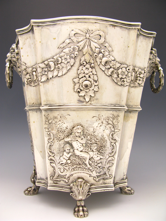 High relief repoussé and chased designs of floral swags above landscapes, lovers and Pan with cherubs decorated this large Hanau sterling silver wine cooler. Dating to the early 1900s, it has a $1,000-$3,000 estimate. Image courtesy of Dirk Soulis Auctions.