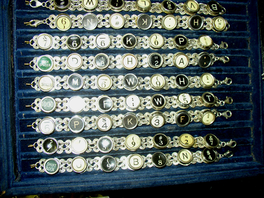 A showboard of charm bracelets made from typewriter keys. Image courtesy Florida Antique Shows/Puchstein Promotions.