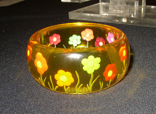 A cast acrylic bangle with back carving and inlay. Image courtesy Florida Antique Shows/Puchstein Promotions.