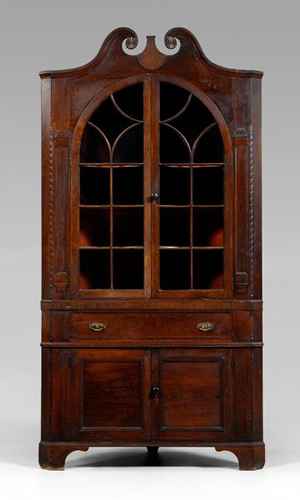 The original blue paint on this Swisegood corner cupboard can be seen under its orange and red painted surface. With rope-carved quarter columns, original brasses and original bracket feet, the cupboard sold for $120,750, a probable new record for a Southern corner cupboard. Image courtesy Brunk Auctions.