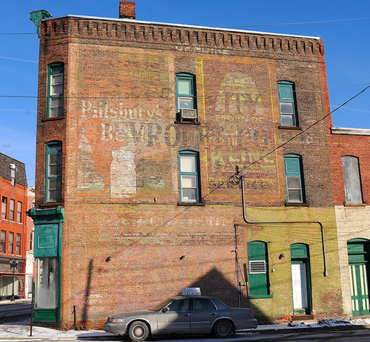 This wall in Gloversville, N.Y. has been repainted several times with brickface ads; the ghost signs that still survive reference everything from Pillsbury flower to the local Chevrolet car dealership.  Photo by Chuck Miller.