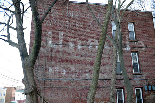 One of several surviving Uneeda Biscuit 'ghost sign' advertisements, this one is on an apartment complex at the corner of 4th and Polk Streets in Troy, N.Y. You can make out the words 'The Perfect Soda Cracker' in upper left, the early Nabisco logo in upper right, and the words 'Uneeda Biscuit,' along with 'National Biscuit Company' at the bottom. Photo by Chuck Miller.