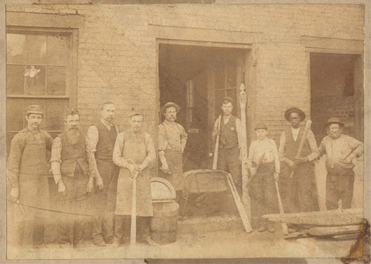 Company founder J. Fred Hillerich is second from the left in this late 1800s photo of the factory crew. His son, Bud Hillerich, stands in the doorway holding a bat on top of a butter churn. Bud made the company's first baseball bat in 1884. Image courtesy Louisville Slugger Museum & Factory.