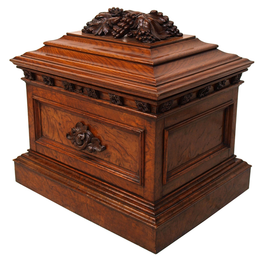 English Mid-19th-century cellaret, oak and burlwood with foliate handles and Black Forest-style leaf-and-grape motif on the stepped, hinged lid. Lead-lined interior holds 12 bottles. Measures 26 inches high by 22 inches wide by 27 inches deep. Estimate $4,000-$6,000. Image courtesy of Austin Auction Gallery.