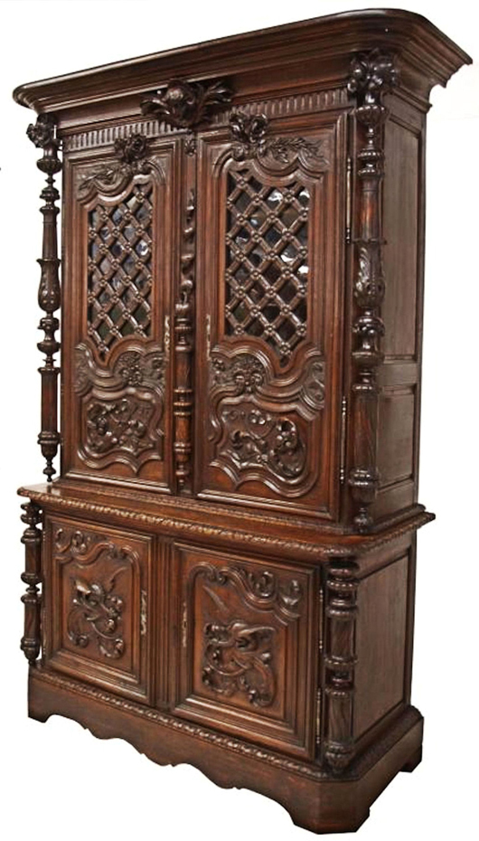 Monumental 99-inch-tall French carved-oak chateau cabinet with doors having floral carved latticework over glazed panels, elaborate turnings and trails of vines, the lower doors carved with griffins amid scrolling clouds. Provenance from the Chateau de Caen, Normandy, France. Estimate $8,000-$12,000. Image courtesy of Austin Auction Gallery.