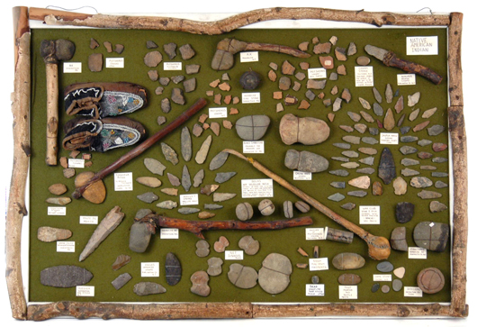 A pair of beaded moccasins is included on this large display board of American Indian artifacts, one of two such displays to be sold at Stephenson's auction.