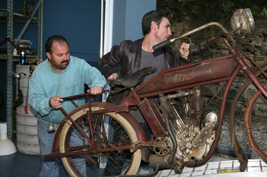 Frank Fritz and Mike Wolfe lifting an early Indian motorbike they bought on the road. Image by Amy Richmond Photography.