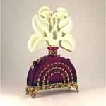 Bearing an 'Ingrid' mark, this 1920s Czechoslovakian perfume bottle is in ruby red crystal, with opaque ivory crystal openwork stopper, gilt metal filigree mount with jewels and Bakelite roses. It is 7 5/8 inches tall and has a $10,000-$12,000 estimate. Image courtesy of Perfume Bottles Auction.