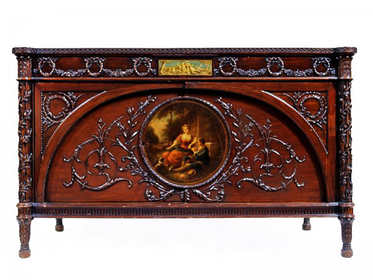 Carved garlands and ribbons and a painted scene depicting a couple in 18th-century dress adorn this mid-19th-century mahogany cabinet. It is 38 1/2 inches high, 63 inches wide and 27 inches deep. The estimate is $6,000-$8,000. Image courtesy of Morton Kuehnert Auctioneers & Appraisers.