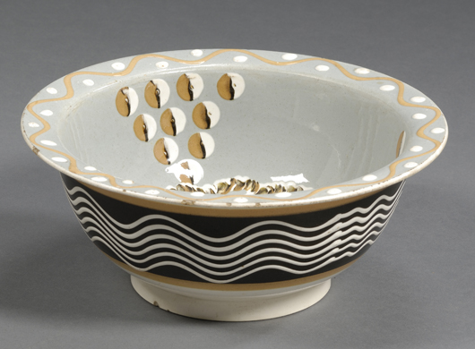 Great graphics - cat's-eyes and earthworm trails on the interior and undulating lines of slip on the exterior - add value to an early 19th-century bowl, which brought $2,607 at the March auction. Image courtesy Skinner Inc.