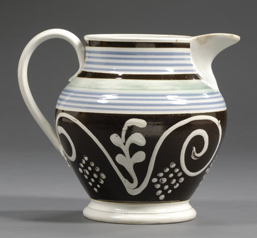 An 8-inch jug, circa 1820, has a broad black band with large scrolls and dots in white slip: $1,896. Image courtesy Skinner Inc.