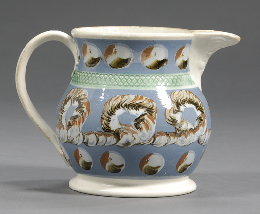 Cat's-eye and earthworm patterns on a slate-blue ground decorate this lot, which brought $2,252. The baluster form jug also features molded designs on the shoulder band, spout and handle terminal. Image courtesy Skinner Inc.