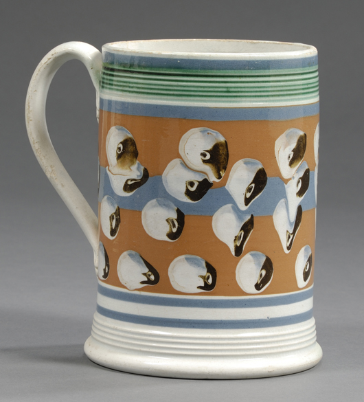 This English quart mug, circa 1830, has a reeded rim and base framing bold cat's-eyes on a blue and tan ground: $1,007. Image courtesy Skinner Inc.