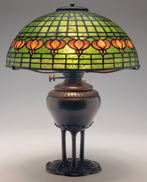 The bronze base of this Tiffany Studios lamp is an unusual form. Topped with a leaded glass shade in the Pomegranate pattern, the lamp is estimated at $15,000-$20,000. Image courtesy of Treadway Gallery.