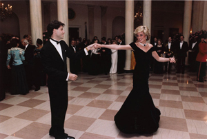 In another iconic black evening gown, Princess Diana dancing with John Travolta in the entrance hall of the White House, Nov. 9, 1985. United States Federal Government photo from the Ronald Reagan Library.