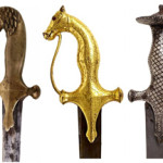 Antique swords in the auction include an early 19th-century Indo-Persian example (center) with gilt grip and guard terminating in three-dimensional horse-head form with jeweled ruby eyes. Austin Auction Gallery image.