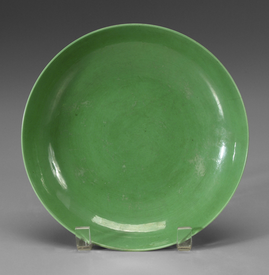 From the Yongzheng period (1723–1735), this Chinese green-glazed bowl is incised with Buddhist symbols. The 8-1/8-inch bowl is estimated at $4,000/$8,000.