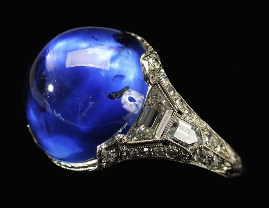 The central cabochon-cut blue sapphire of this exceptional Art Deco ring is a medium violet blue color with excellent transparency. Its platinum mount is accented with 36 diamonds and is sized 5-3/4. Est.: $10,000/$20,000.
