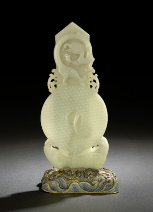 A complex carving of precious white jade soared to $334,000 in May at a New Orleans Auction Galleries sale. The 18th century pi disk is topped by a carved dragon; twelve symbols are carved in the tablet on the reverse. Courtesy New Orleans Auction Galleries
