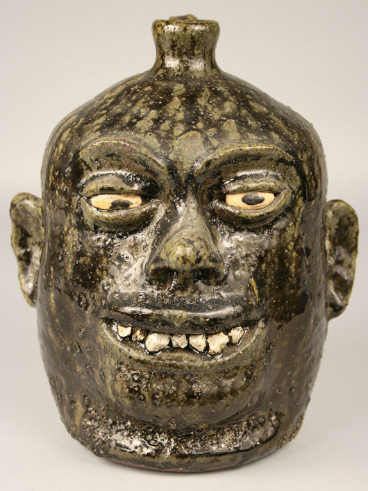 Whimsical face jugs were a specialty of folk art potter Lanier Meaders (1917-1998) of White County, Ga. This signed example with painted eyes, rock teeth, and a dark olive glaze brought $1,475. Image courtesy Case Auctions, Knoxville, Tenn.