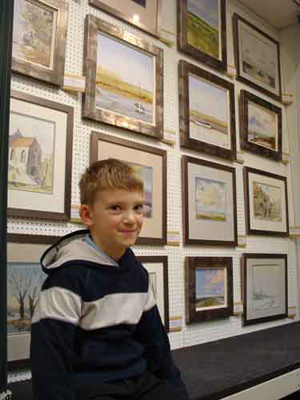 8-year-old Kieron Williamson is the talk of the art trade. He sells his work through Picturecraft Gallery & Exhibition Centre, where this picture was taken. Image copyright Picturecraft Gallery & Exhibition Centre.