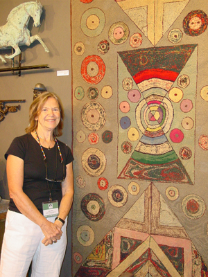 "Judith Milne (Judith & James Milne, New York City) with a 1930s hooked rug in a unique design - ""not a pattern."" $2,800. Photo copyright Catherine Saunders-Watson."
