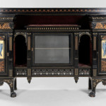 This 58¾ inch by 87¼ inch by 18¾ inch signed Herter Brothers cabinet with gilt and ebonized surfaces has a presale estimate of $15,000-$25,000. A cabinet with the same form but different ornamentation is illustrated in Herter Bros. Furniture and Interiors for a Gilded Age. Brunk Auctions image.