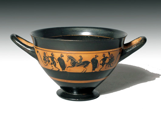>A horse and rider are flanked by two draped figures and two satyrs on either side of this Attic black-figure skyphos, circa 530 B.C. Excluding the handles, it measures 4 7/8 inches in diameter and is estimated at $6,500-$8,000. Image courtesy of Artemis Gallery Live.com.