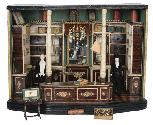 German tobacco shop room box, late-19th century and almost certainly a Christian Hacker, featuring deluxe appointments such as faux-marble columns, a Schweitzer chandelier, glass-topped cigar display box full of miniature faux cigars, two finely dressed circa-1880 Simon & Halbig gentlemen dolls, 21¼ inches long by 15½ inches tall by 15½ inches deep, estimate $8,000-$12,000. Noel Barrett image.