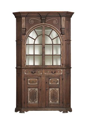 Rare black walnut carved, sulphur and pewter-inlaid, glazed corner cupboard, Lancaster County, Pa., circa 1790. Estimate $100,000-$150,000. Image courtesy of Skinner Inc.
