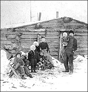 A 19th-century photo of a Minnesota family in front of their log cabin. Photo courtesy of the Minnesota Historical Society.