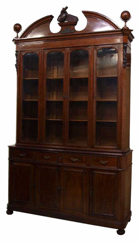 Spanish Alfonsino mahogany bookcase, circa 1890, a carved anchor, barrel and trunk rest at the center of the split pediment with carved globes at either side, 121 inches high, 70 inches wide, 20 inches deep. Provenance: From the estate of a prominent family, Madrid, Spain, the patriarch, a sea captain, had the cabinet custom made. Estimate: $2,000-$4,000. Image courtesy of Austin Auction Gallery.