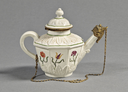 Vezzi Porcelain bronze mounted teapot and cover, Venice, Italy, circa 1725, with molded acanthus leaf borders and paneled sides polychrome enamel decorated with flowers, green enamel trim lines, 5 inches high. Estimate $20,000-$30,000. Image courtesy of Skinner Inc.