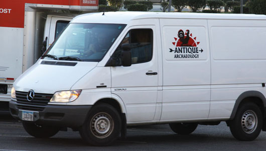 The American Pickers' Mercedes-Benz van, with Mike Wolfe at the wheel and Frank Fritz riding shotgun, pulls into the parking lot at Affiliated Auctions' gallery. The logo on the van, Antique Archaeology, represents Wolfe's company located in LeClaire, Iowa. Image courtesy of Affiliated Auctions.