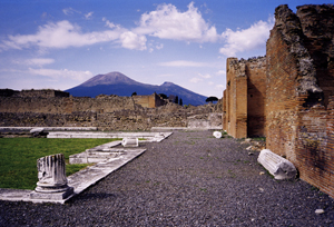 Mount Vesuvius as seen from the ruins of Pompeii, which was destroyed in the eruption of AD 79. The active cone is the high peak on the left side. Image courtesy of Wikimedia Commons.