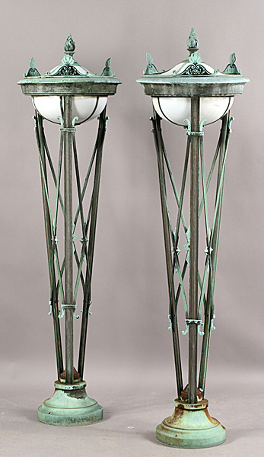 Pair of bronze Regency-style torchieres having x-form stands supporting leaded glass globes with flame finials, circa 1900. Estimate: $2,000-$3,000. Image courtesy of Kamelot Auctions.