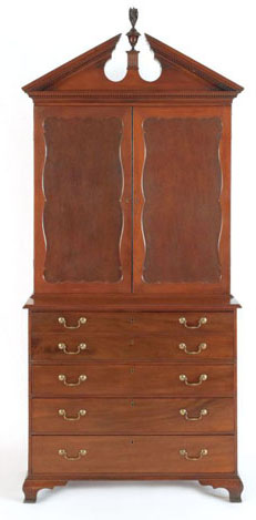 """The Chief Justice Tristram Burgess Rhode Island Chippendale mahogany secretary desk, ca. 1795, in two parts, the upper section with a broken pediment top centering on a flame finial above two doors with scalloped sunken panels, resting on a base with butler's desk above three long drawers, all supported by ogee bracket feet, 106"""" h., 44"""" w. $10,000-$15,000. Pook & Pook image."""