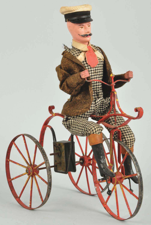 French tin 3-wheel cycling toy, clockwork, 11 inches long, with dressed wood and composition figure, estimate $2,000-$4,000. Morphy Auctions image.