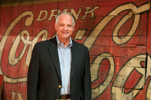 Larry Schmidt represents the fourth generation of his family to work in the Coca-Cola bottling business. In the background is a side of a barn painted with the Coca-Cola logo. Image courtesy of the Schmidt Museum of Coca-Cola Collectibles.