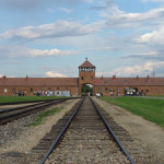 View of the main gate at former Nazi death camp of Birkenau. August 2006 photo by Angelo Celedon, licensed under the Creative Commons Attribution-Share Alike 2.5 Generic license.