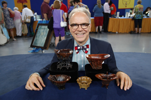 Antiques Roadshow appraiser Lark Mason with the collection of Chinese rhinoceros-horn cups appraised at the TV show's stop in Tulsa, Oklahoma. Image copyright Antiques Roadshow, used by permission.