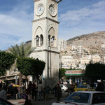 A clock tower and adjacent tourist center are at Ash-Shuhada Square in downtown Nablus. Image by Tiamat. This file is licensed under the Creative Commons Attribution-Share Alike 3.0 Unported license.